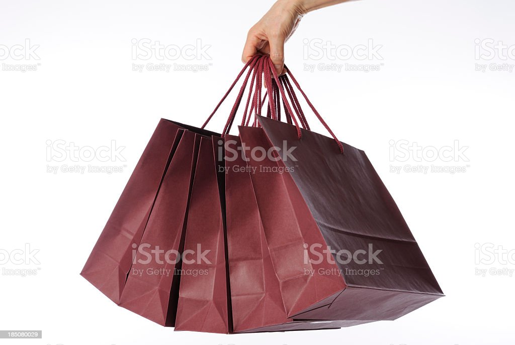 Isolated shot of hand carrying shopping bags against white background royalty-free stock photo