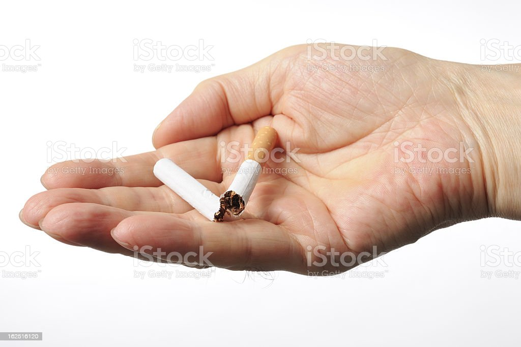 Isolated shot of holding a broken cigarettes on white background royalty-free stock photo