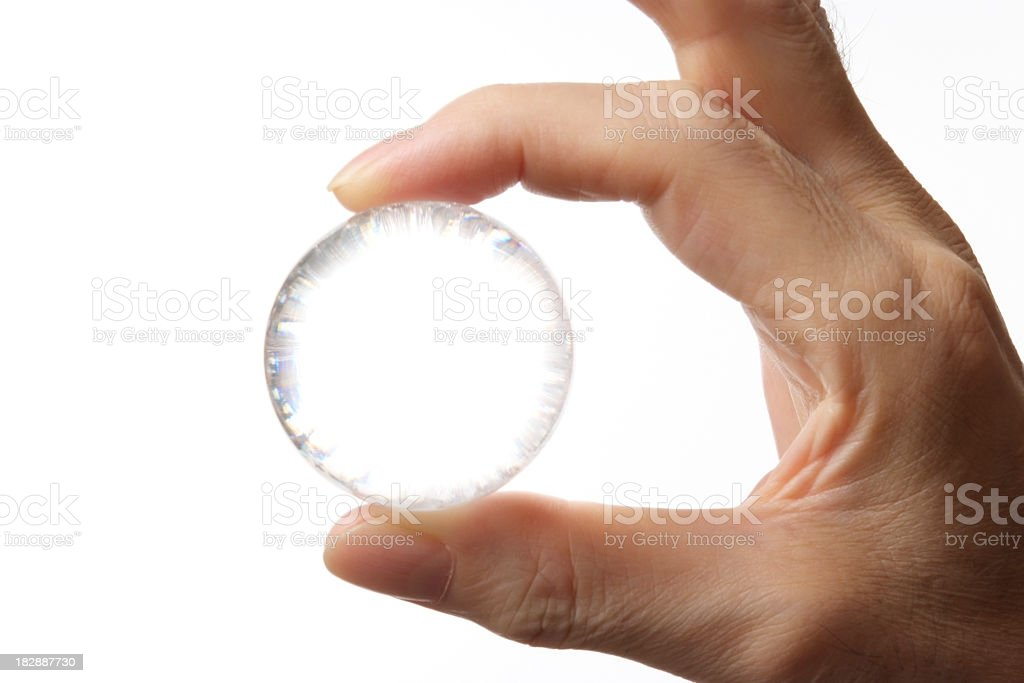 Isolated shot of holding a glass ball ageinst white background stock photo