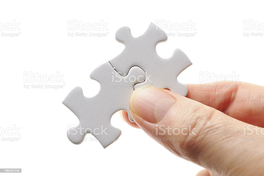 Isolated shot of holding a Jigsaw puzzle on white background royalty-free stock photo