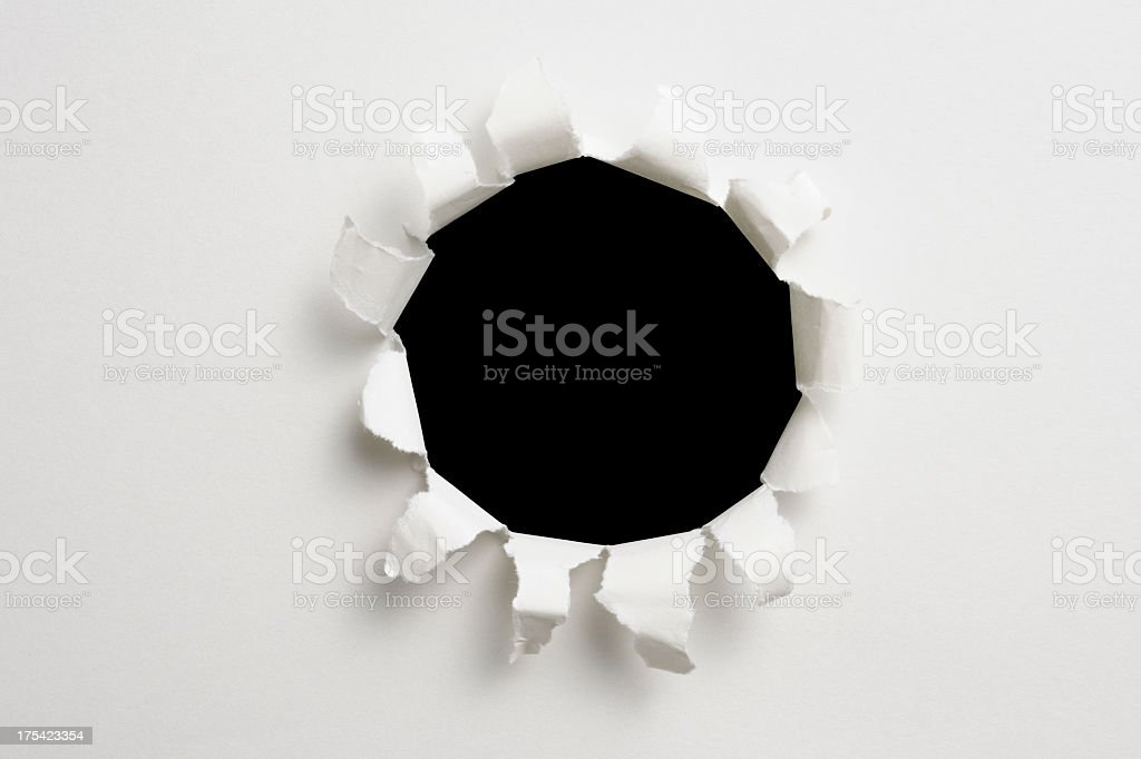 Isolated shot of hole in white paper on black background stock photo