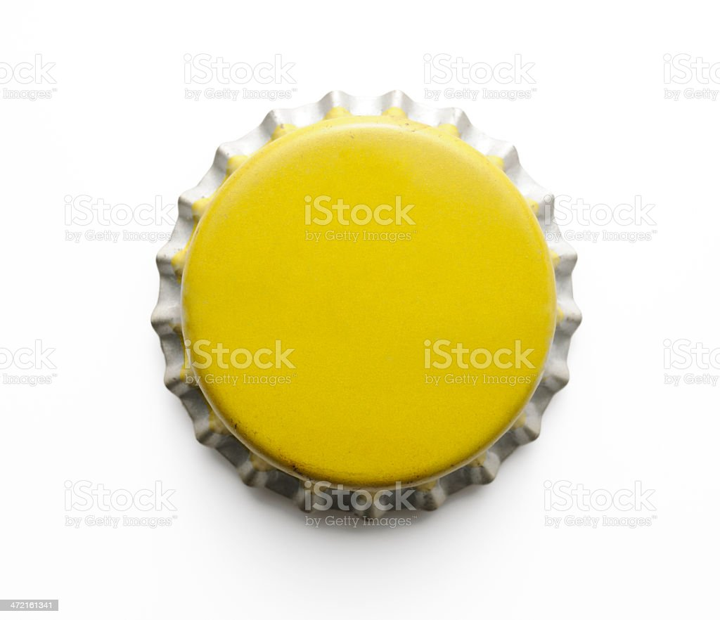Isolated shot of old yellow metal bottle cap on white royalty-free stock photo