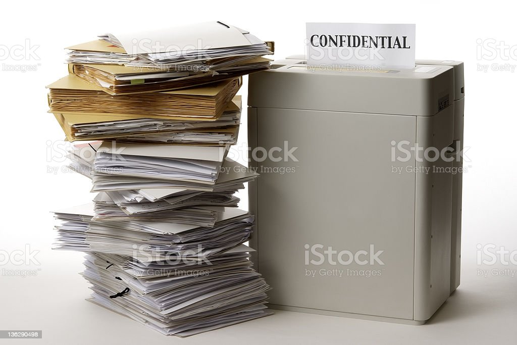 Isolated shot of paper shredder with documents on white background stock photo