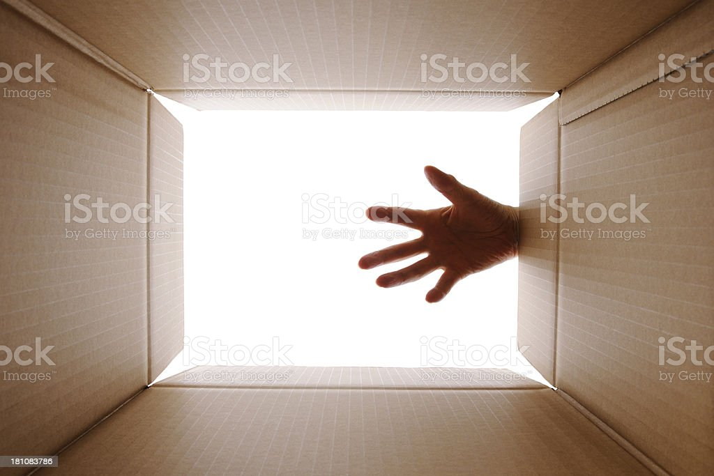 Isolated shot of reaching in cardboard box against white background royalty-free stock photo