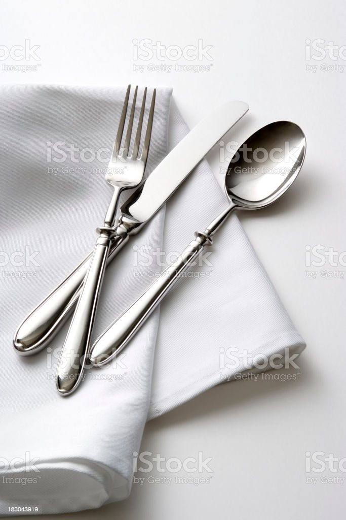 Isolated shot of silverware with table napkin on white background royalty-free stock photo