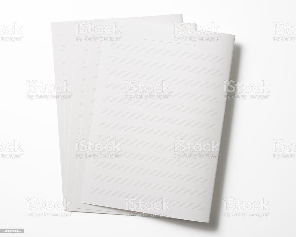 Isolated shot of stacked blank sheet music on white background royalty-free stock photo