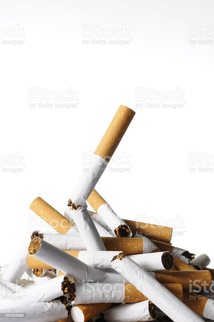 Isolated shot of stacked broken cigarettes against white background stock photo
