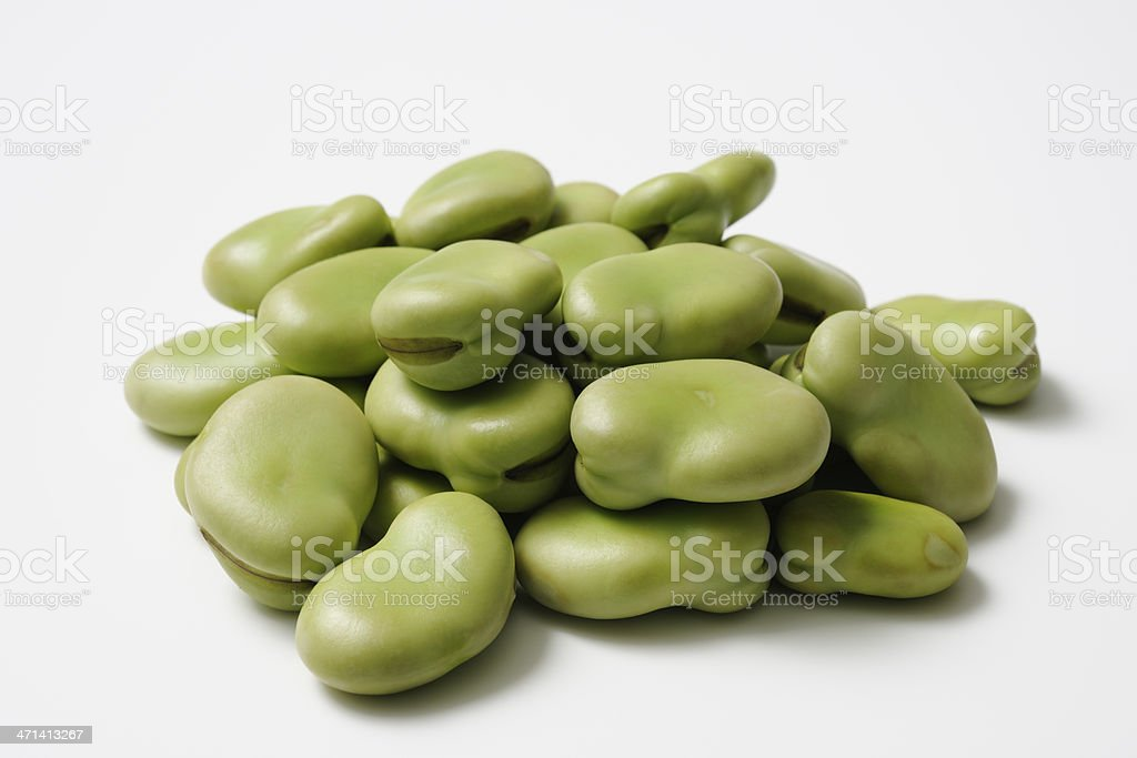 Isolated shot of stacked uncooked broad beans on white background royalty-free stock photo