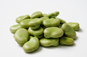 Isolated shot of stacked uncooked broad beans on white background
