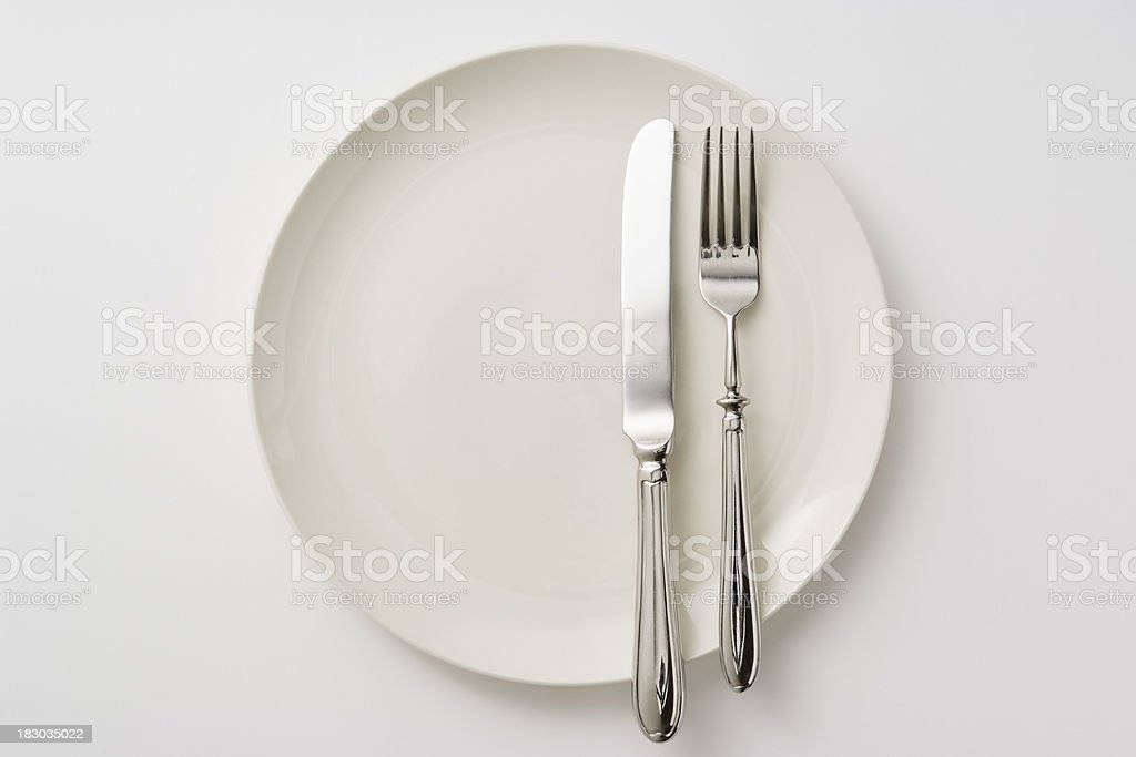 Isolated shot of white plate with silverware on white background royalty-free stock photo