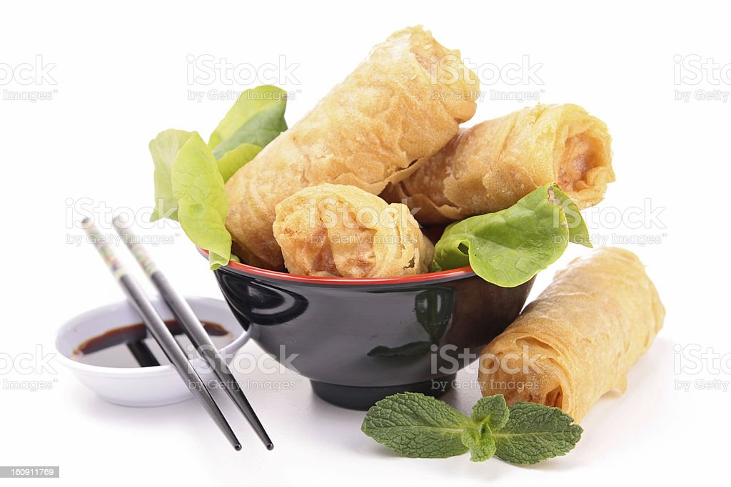 Isolated spring rolls in the mug and two Chinese sticks stock photo