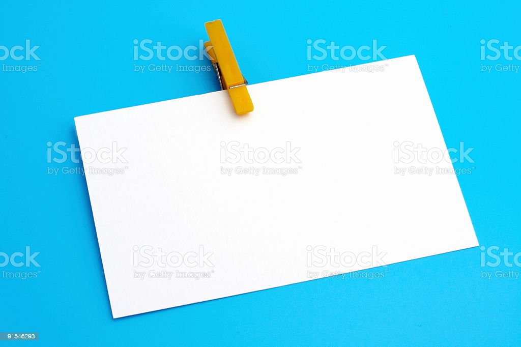 Isolated white paper with yellow clamp on blue background royalty-free stock photo
