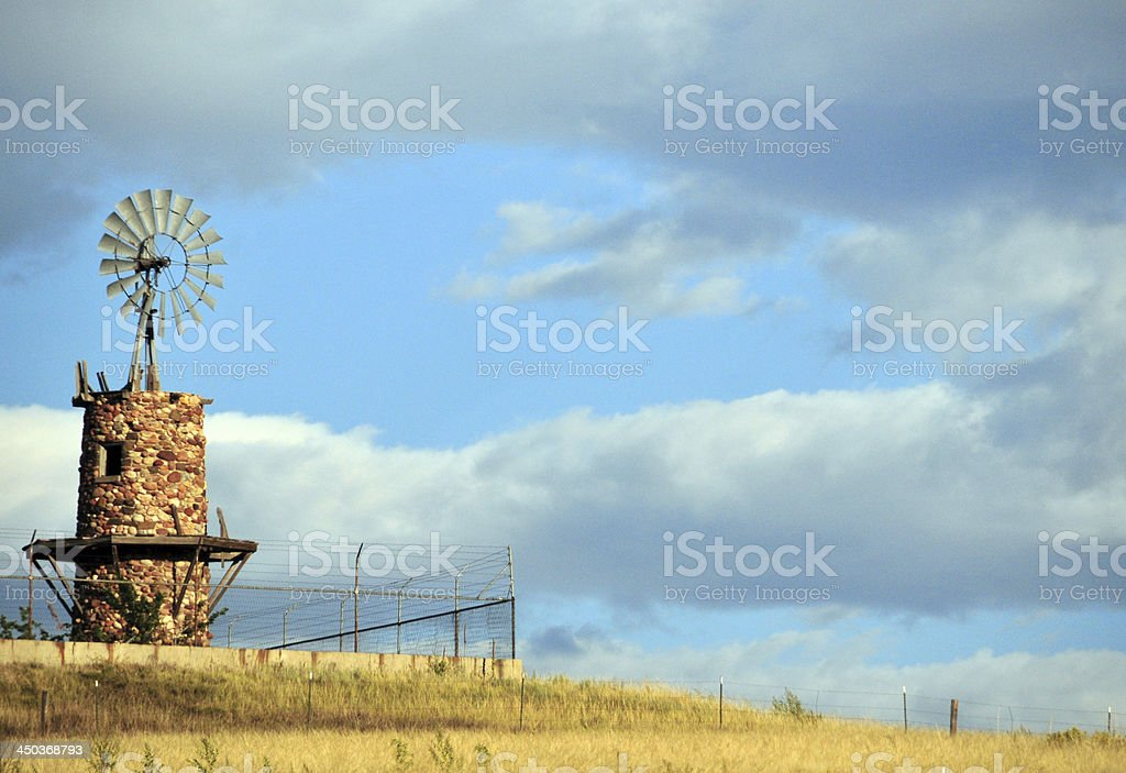 Isolated windmill on a hilltop with field on a clear day stock photo