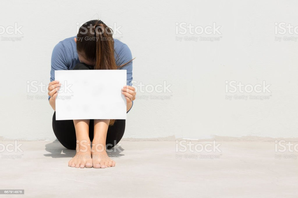 Isolated woman holding blank white sign with her head buried in her knees stock photo
