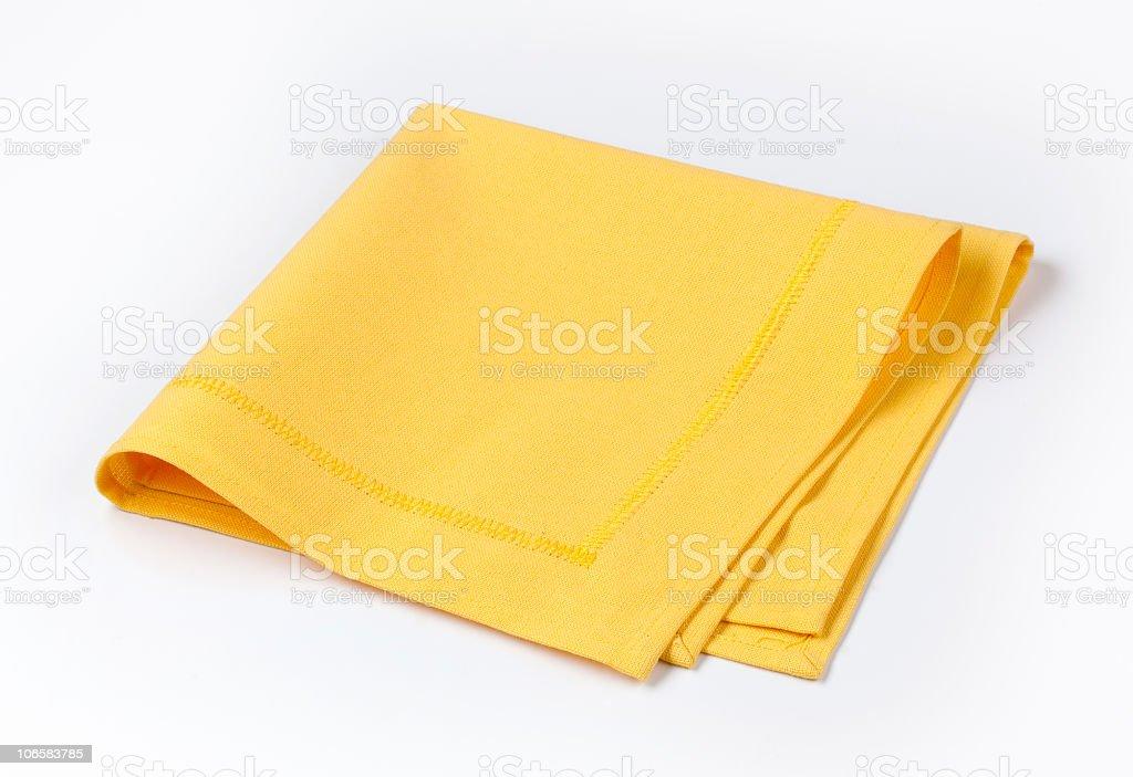 Isolated yellow napkin twice folded on white background stock photo