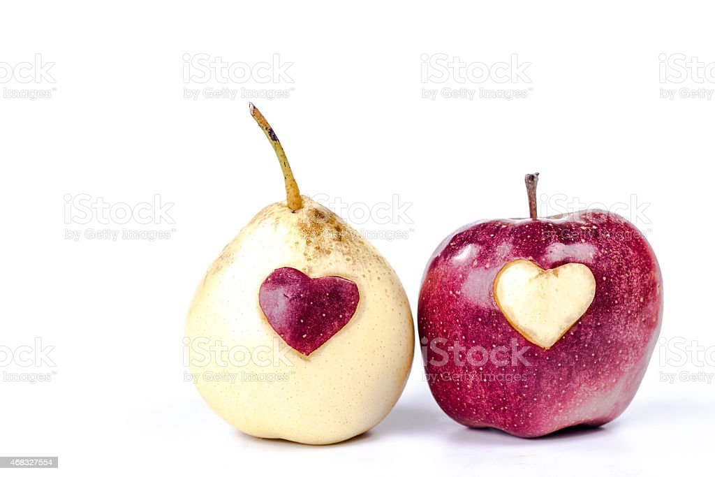 isolated yellow pear  and red apple with carved heart stock photo