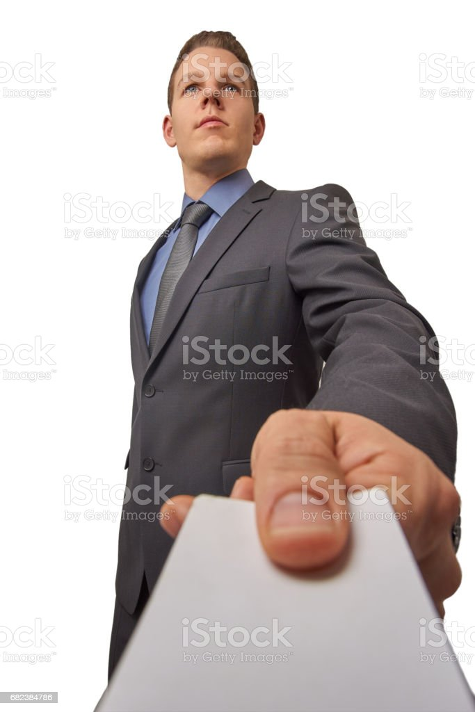 Isolated young attractive successful seriously businessman hands over a business card. Low angle shot with copy space. stock photo