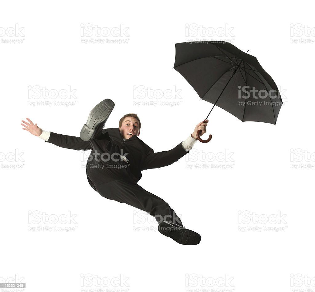 Isolated young businessman free falling while holding an umbrella stock photo