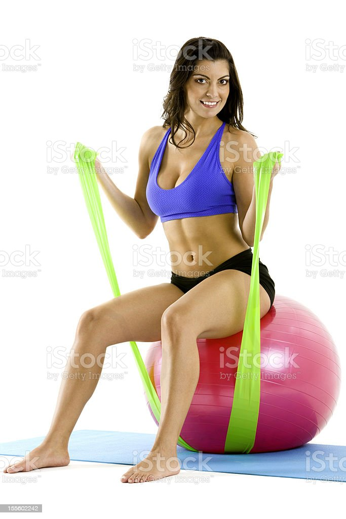 Isolated young woman doing Pilates with slings on fitness ball royalty-free stock photo