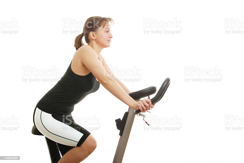 Isolated young woman sitting on a spinning bicycle royalty-free stock photo