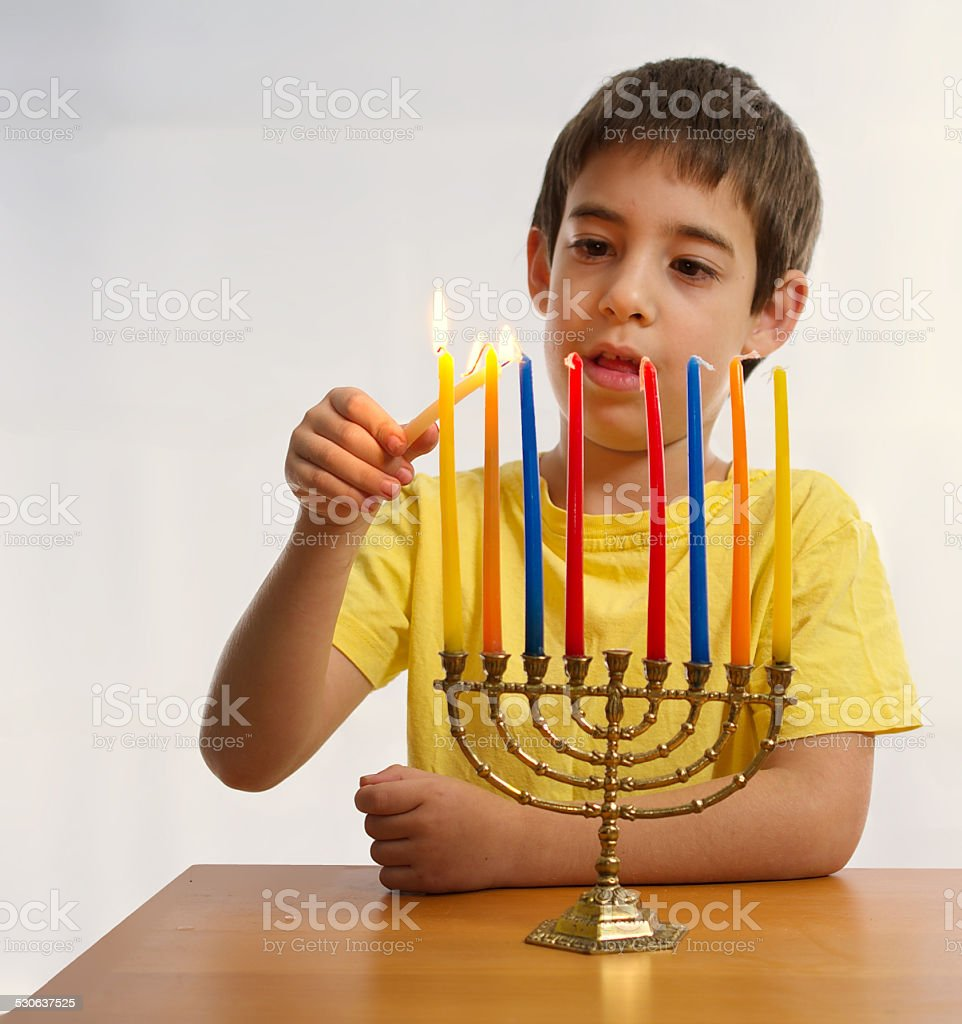 Israeli boy lighting a Hannukah Menorah stock photo