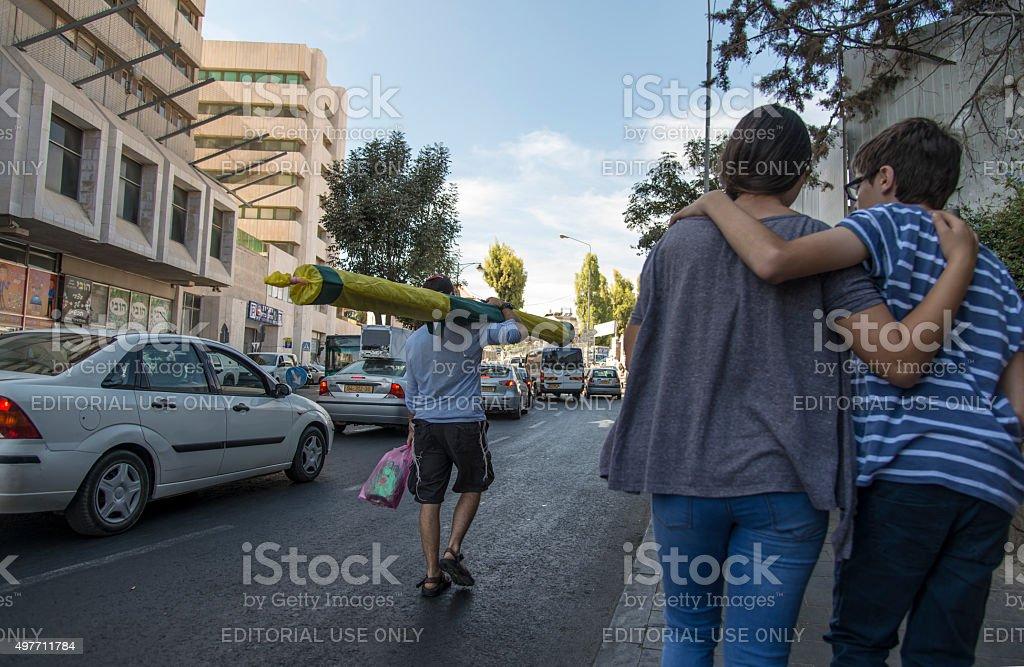 Israeli man carry sukkah people walking in street stock photo