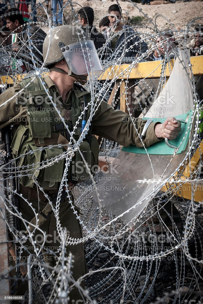 Israeli soldier with shield at West Bank barrier in Bil'in stock photo
