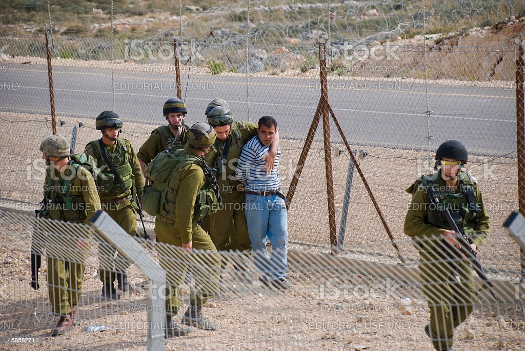 Israeli soldiers arresting a Palestinian man in Bil'in stock photo