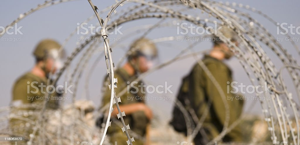 Soldiers on Patrol through razor wire royalty-free stock photo