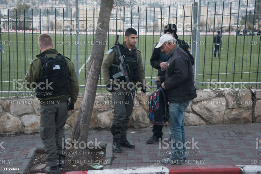 Israeli soldiers stopping Palestinian at checkpoint stock photo