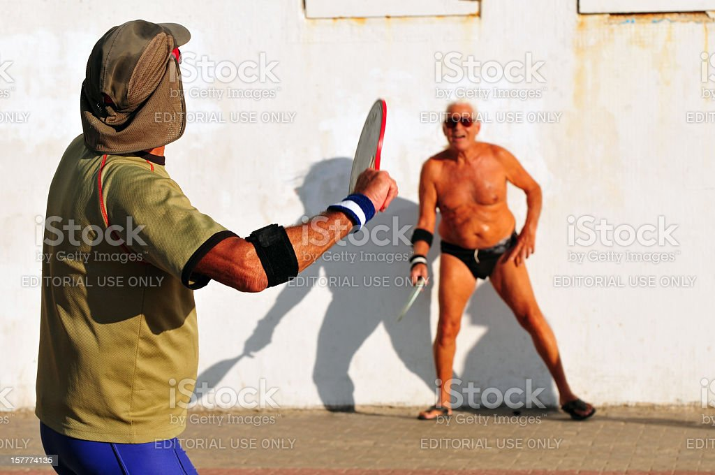 Two men playing matkot in Israel royalty-free stock photo