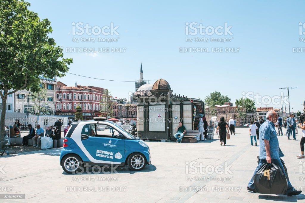 Istanbul, June 15 2017: Municipal tourist team. Blue Smart car and people at Eminonu square in the middle of the day. stock photo