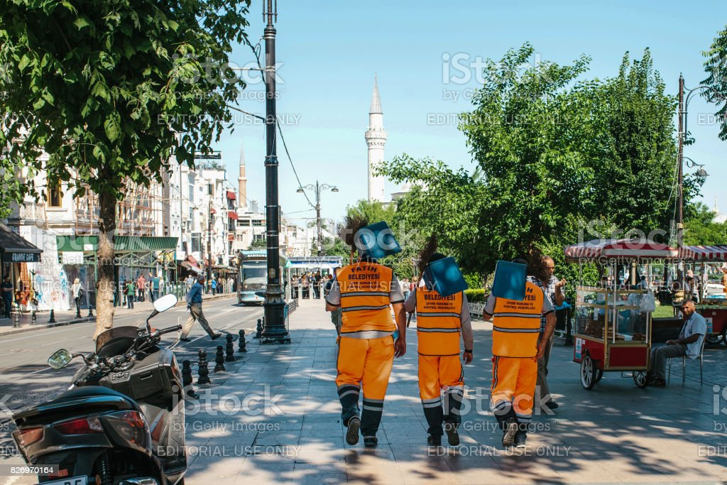 Istanbul, June 15, 2017: Three street janitors in bright orange uniforms are walking down the street holding brooms and dust pans. stock photo