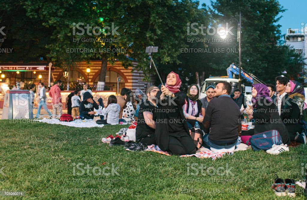 Istanbul, June 16, 2017: Many people of the Islamic religion take food in the plaza sultanahmet next to the blue mosque in the evening in the Ramadan. The girl makes selfie a memory with her family. stock photo