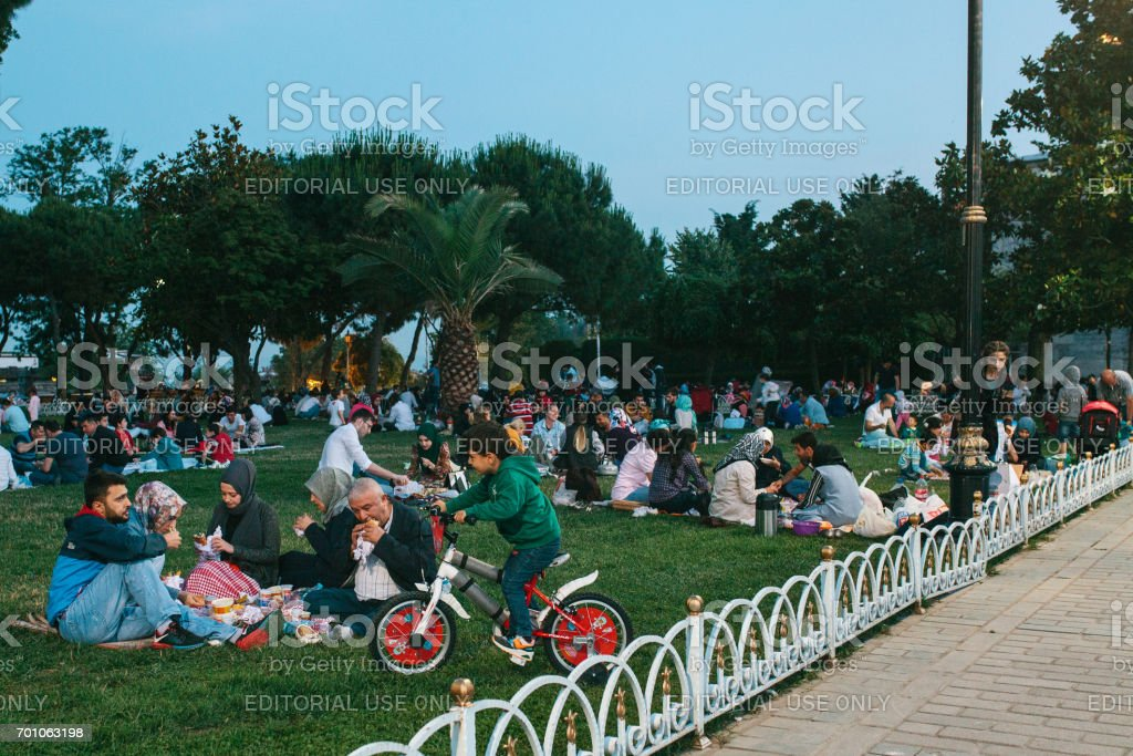 Istanbul, June 16, 2017: Many people of the Islamic religion take food on the Sultanahmet square next to the blue mosque along with their relatives at the time allowed in the Ramadan fast. Ramazan. stock photo