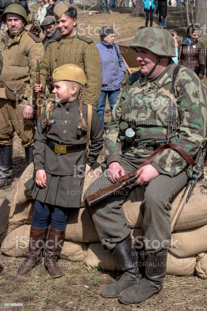 istorical reconstruction of the battles of World War II. German soldiers and the girl in the form of the Soviet army rest and laugh after reconstruction. stock photo