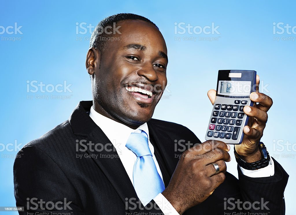 It all adds up! Handsome, smiling businessman with calculator royalty-free stock photo
