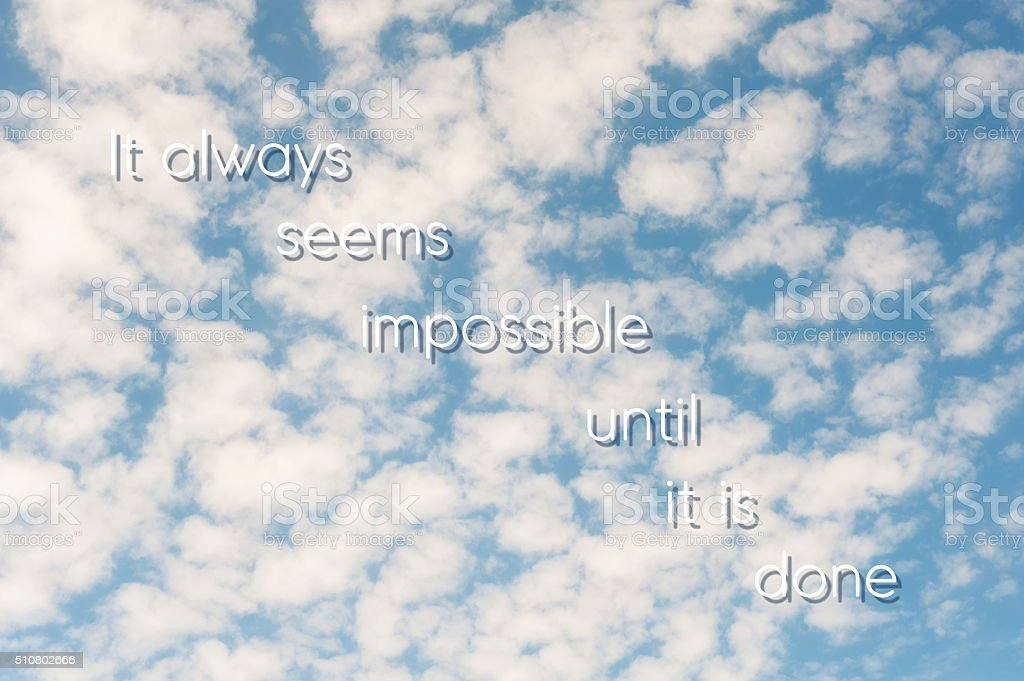It always seems impossible until it is done. Blue cloudy sky. stock photo