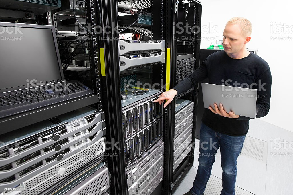 It consultant monitors blade servers in datacenter stock photo