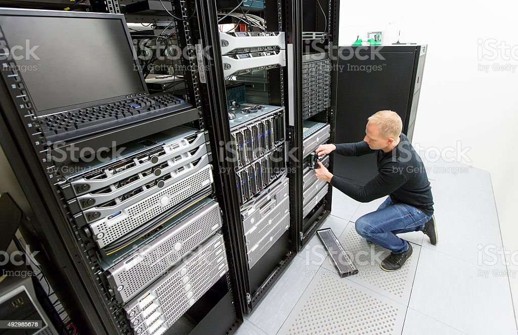 It consultant replace harddrive in datacenter stock photo