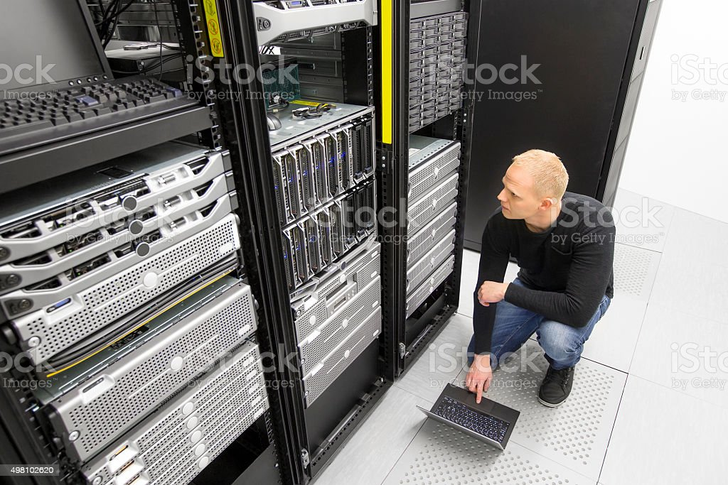 It consultant working with blade servers in datacenter stock photo
