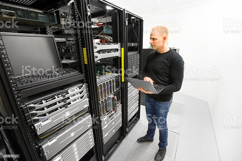 It engineer maintains servers in datacenter stock photo