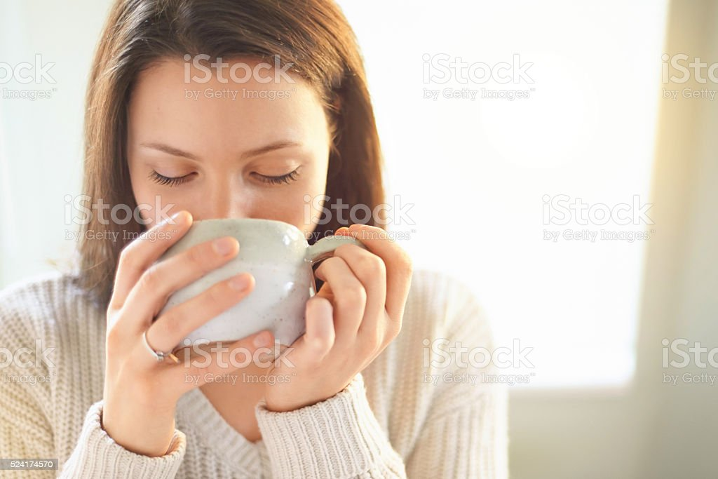 Shot of a woman drinking coffee at home
