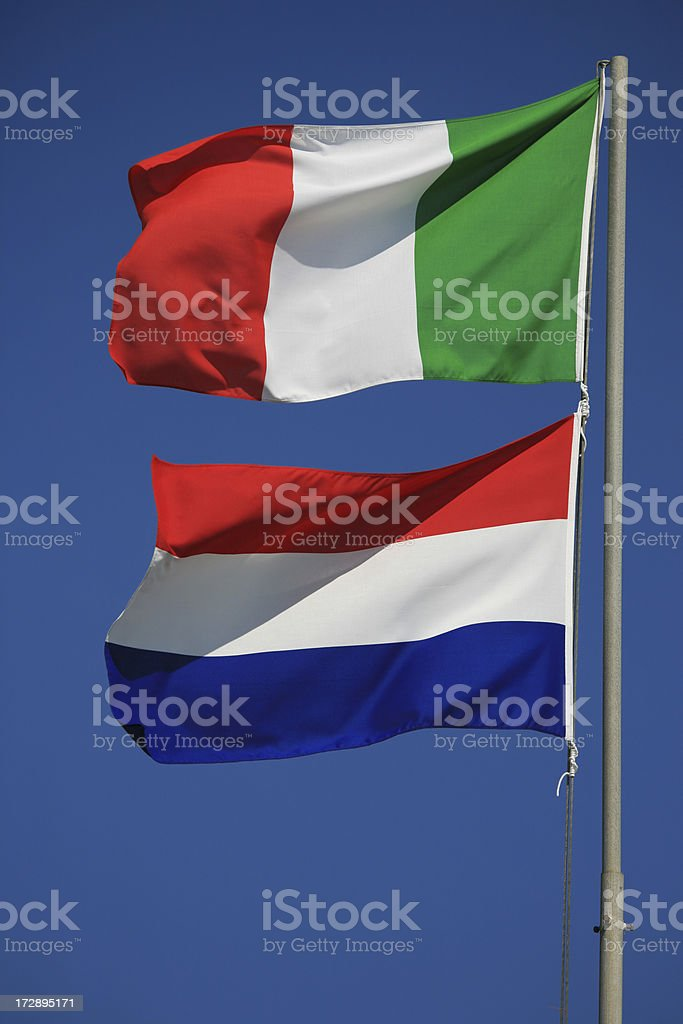 Italian and Dutch flags together on a pole stock photo