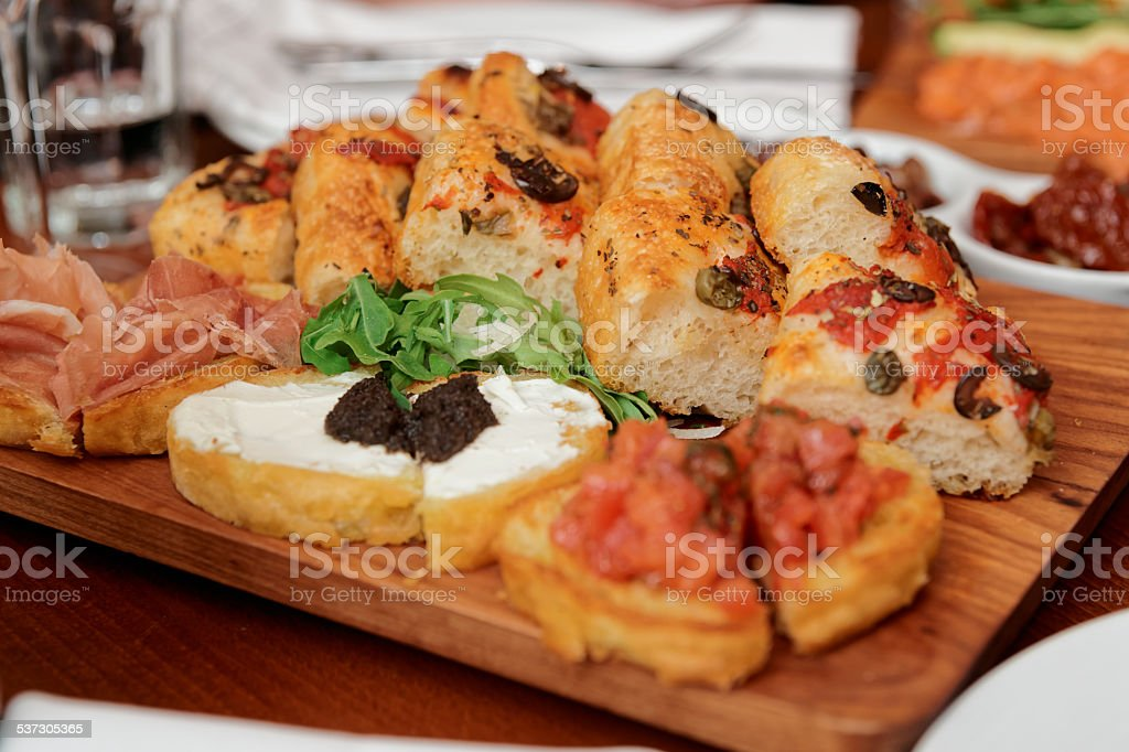 Italian appetizers on wooden plank stock photo