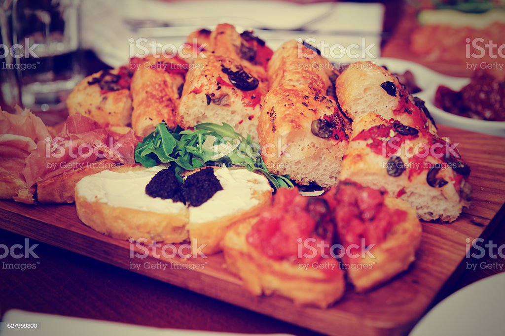 Italian appetizers on wooden plank, toned stock photo