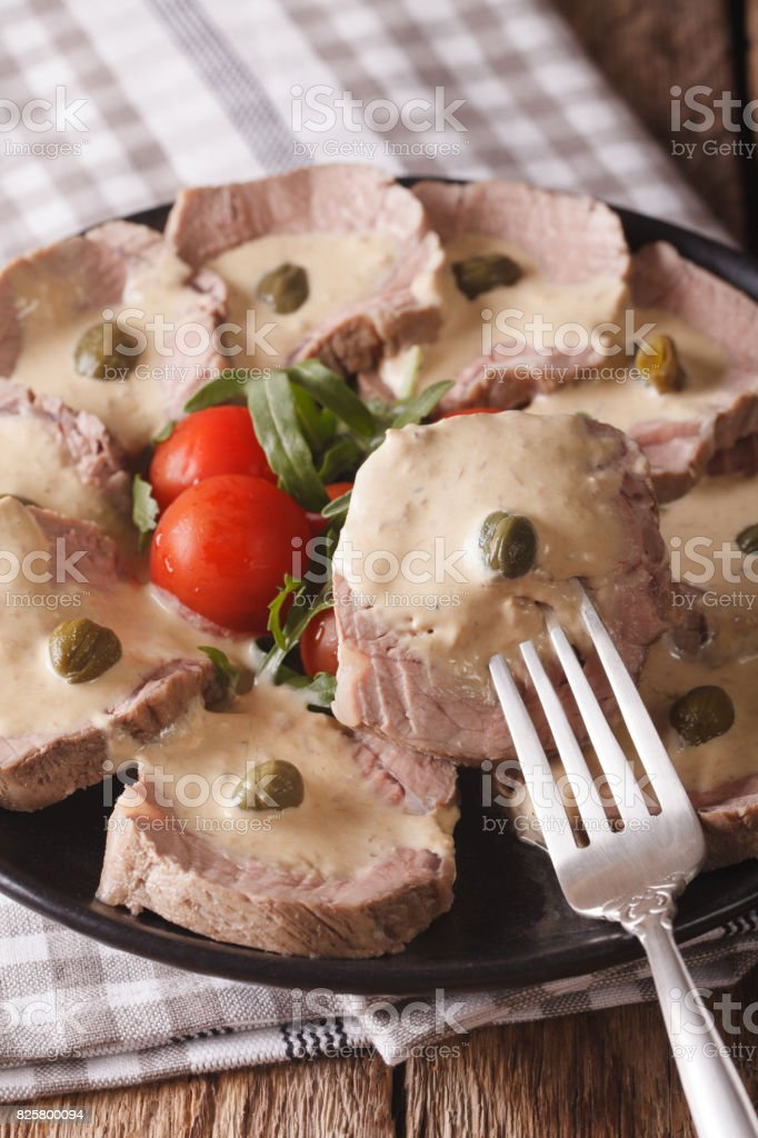 Italian beef with tuna sauce close-up. vertical stock photo