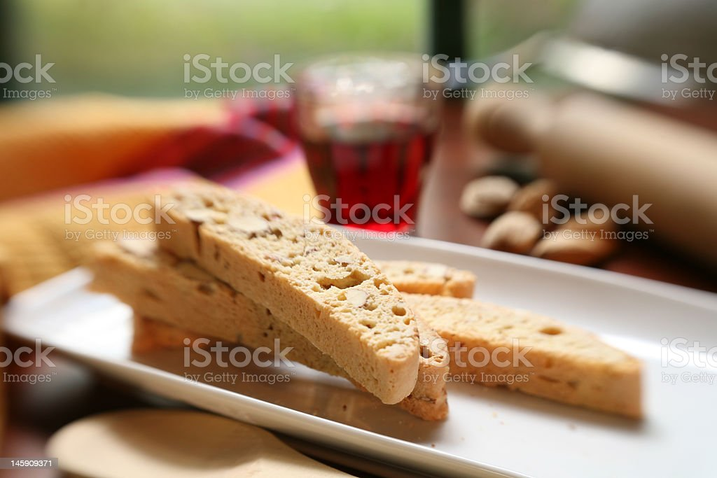 Italian biscotti on a plate and red wine in background royalty-free stock photo