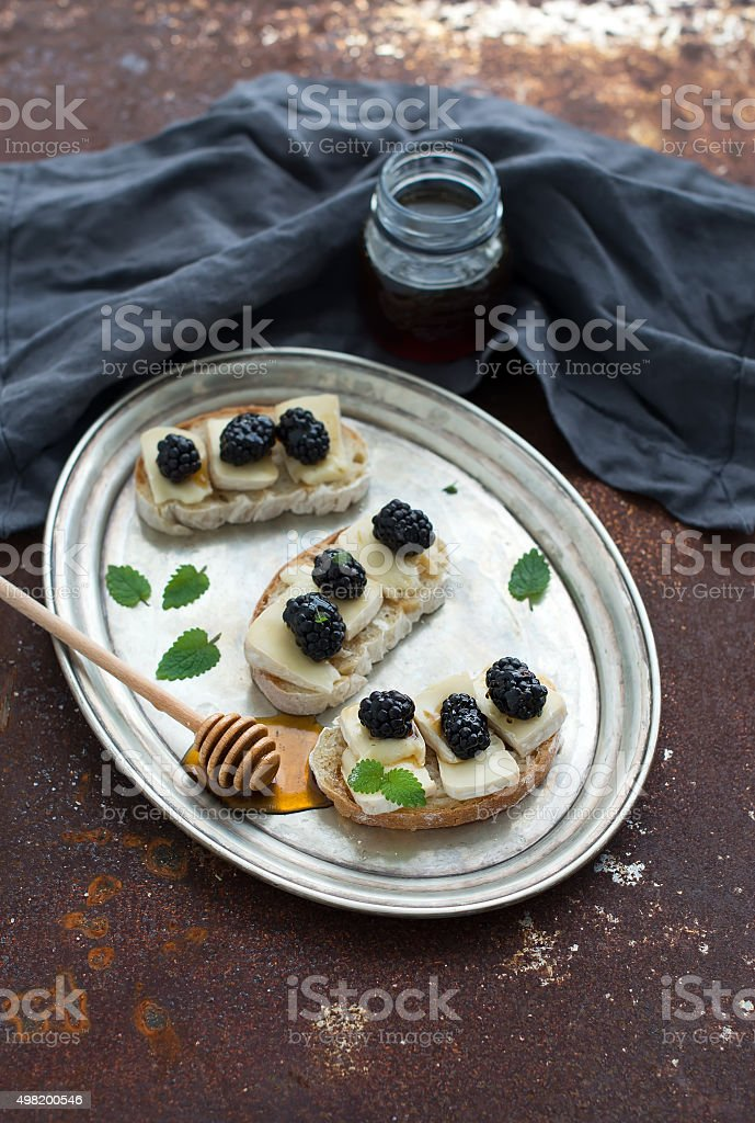 Italian bruschetta sandwich with brie cheese, honey and blackberry on stock photo