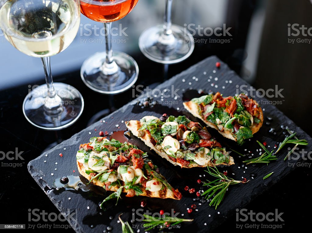 Italian bruschetta with roasted tomatoes, mozzarella cheese and herbs stock photo